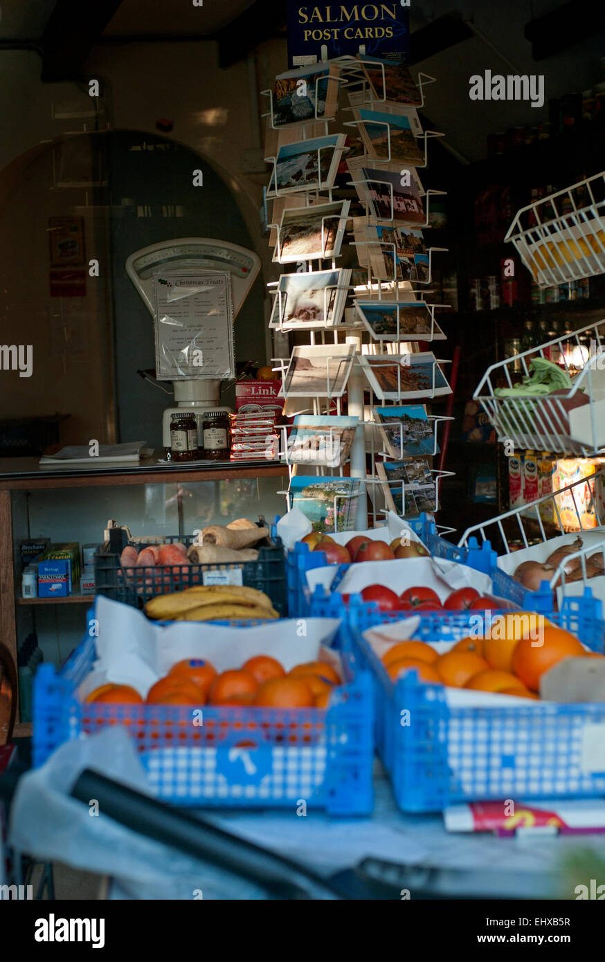 Small shop postcard carousel with weighing machine and fruit and veg in foreground - Stock Image