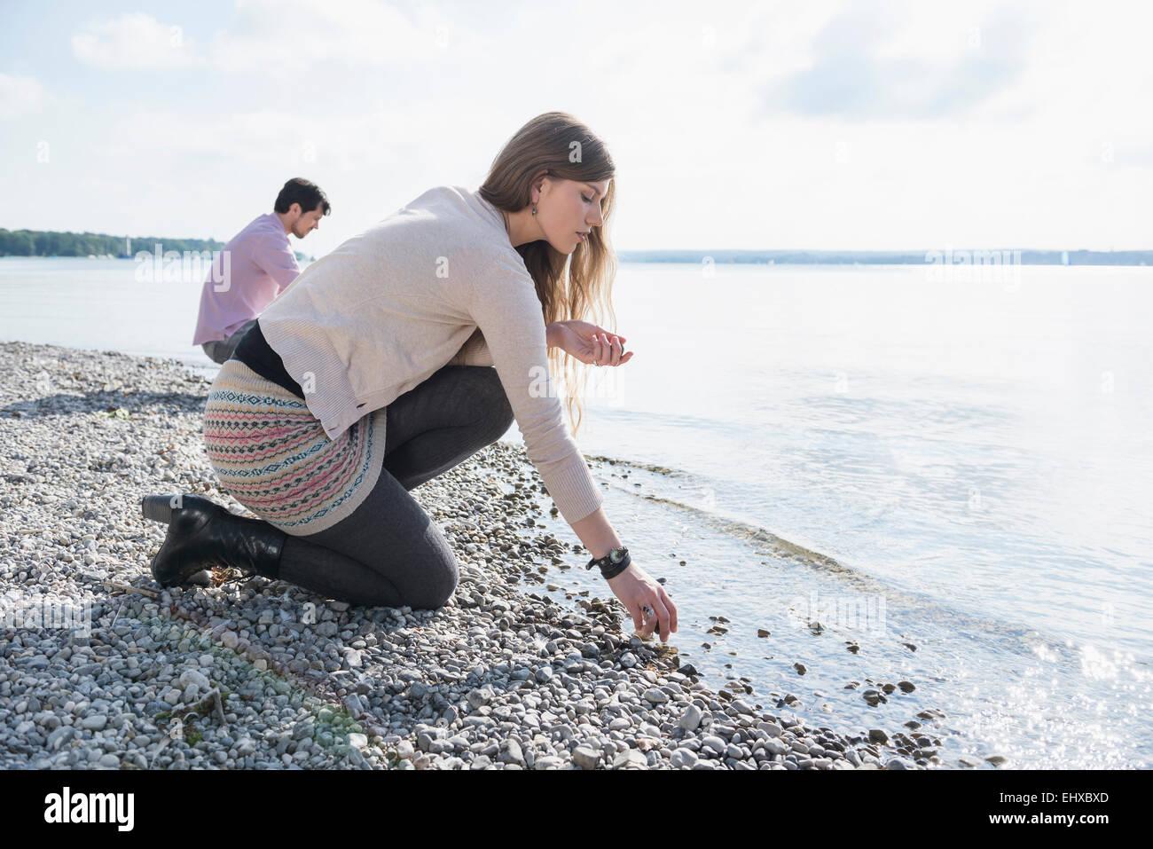 Young couple lake shore gathering pebbles - Stock Image