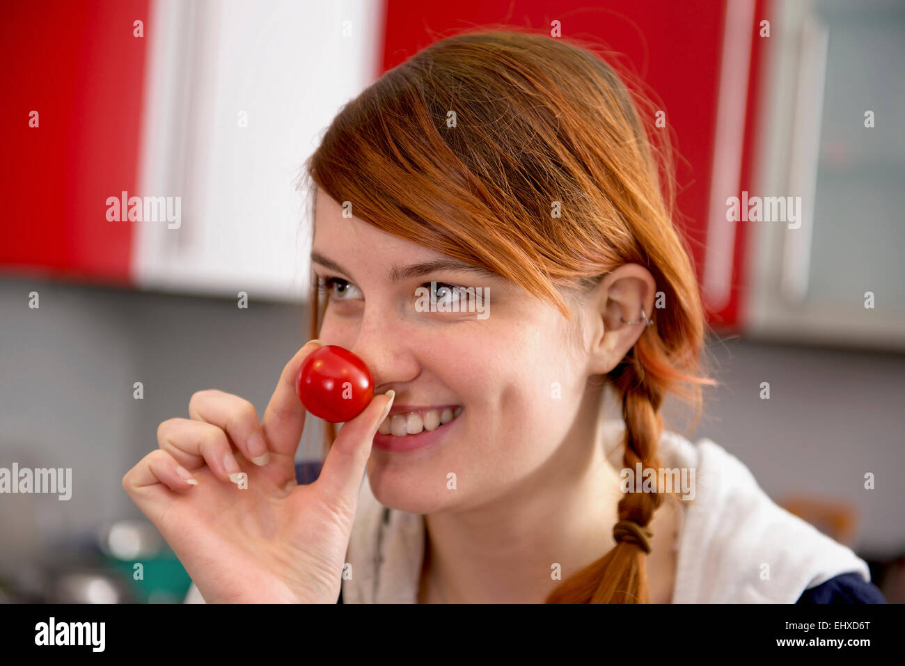Young woman wearing clown nose, Munich, Bavaria, Germany - Stock Image