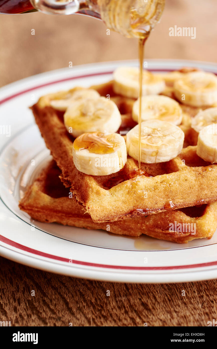 Puring maple syrup over quinoa waffles with banana slices and maple syrup - Stock Image
