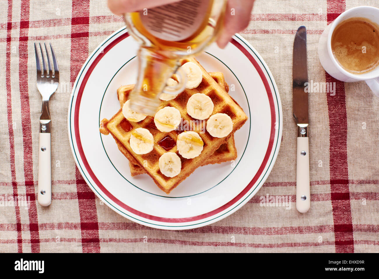 Quinoa waffles with banana slices and maple syrup - Stock Image