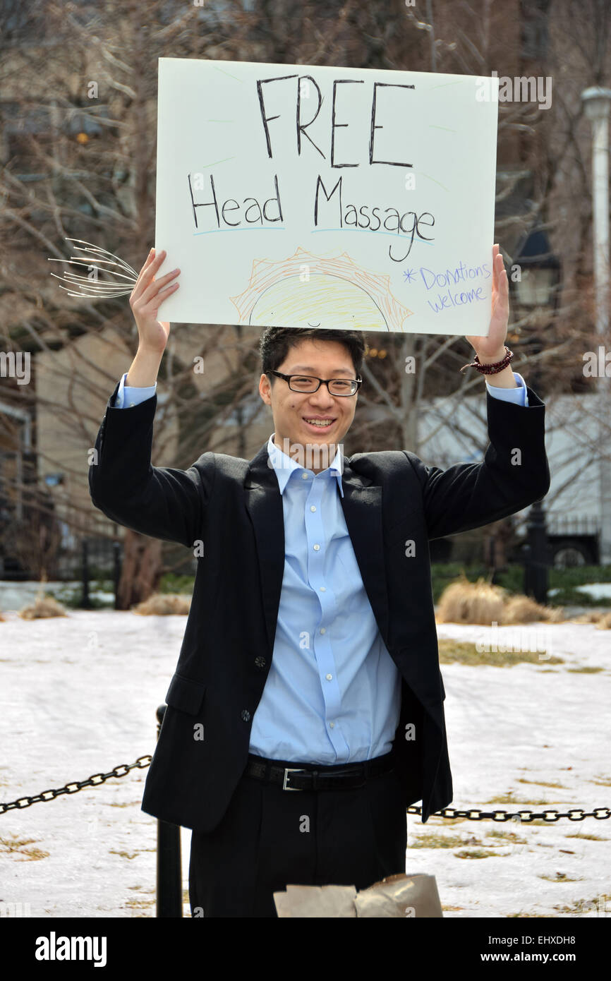 An Asia busker in Washington Square Park in Greenwich Village, New York City offering free head massages & soliciting - Stock Image