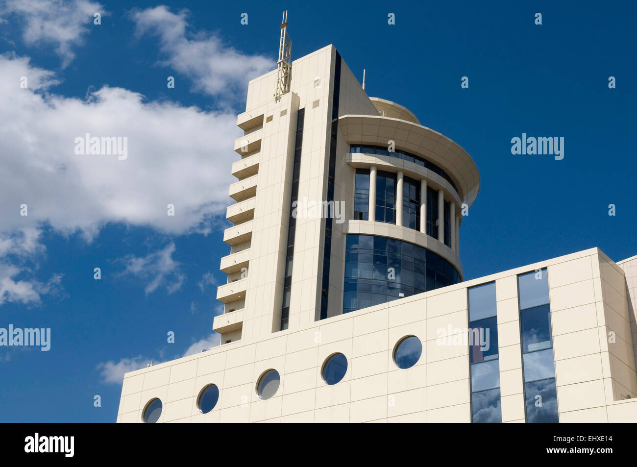 White modern building is situated against the blue sky background. Clouds and sky are reflected in the windows. Stock Photo