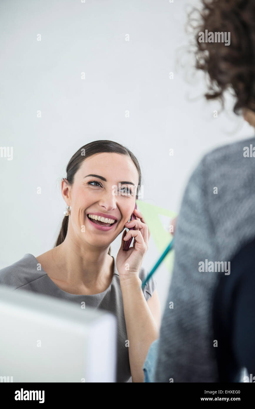 Businesswoman talking on mobile phone in an office, Munich, Bavaria, Germany Stock Photo