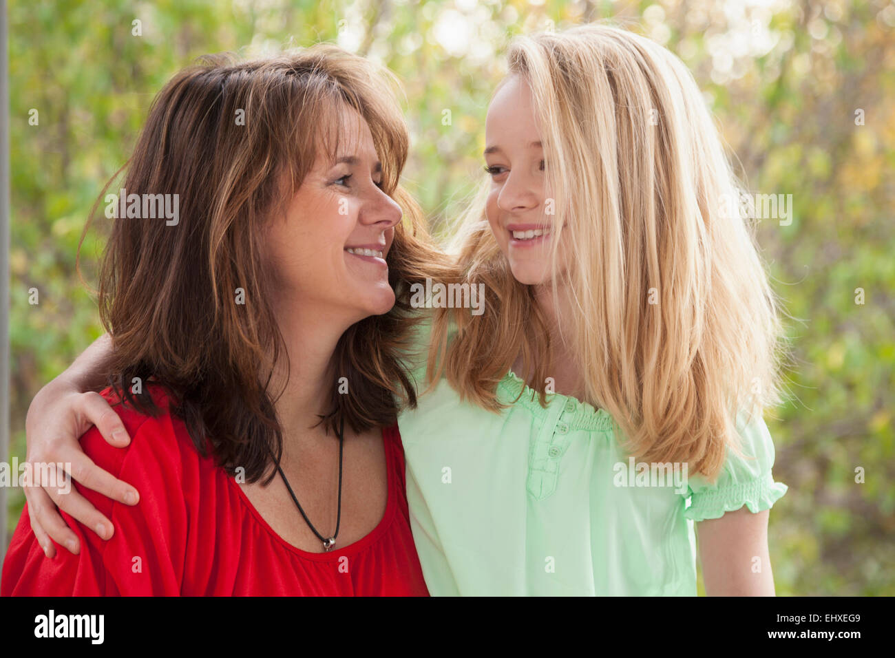 Girl hugging her mother and smiling, Bavaria, Germany - Stock Image