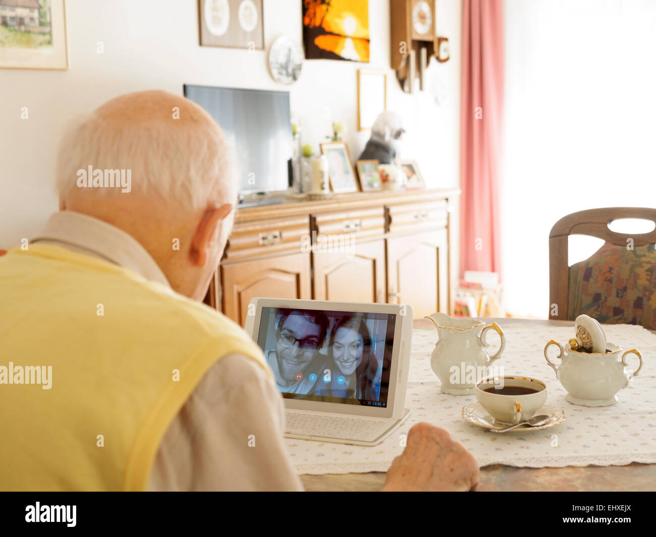 Grandfather videoconferencing with grandchildren via digital tablet - Stock Image