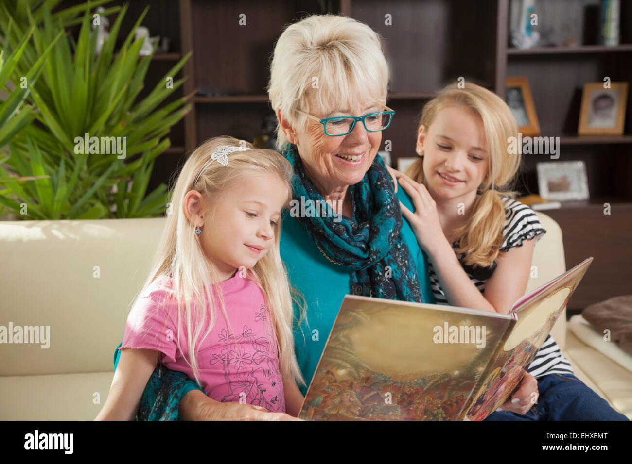 Grandmother reading book to her granddaughters, Bavaria, Germany - Stock Image