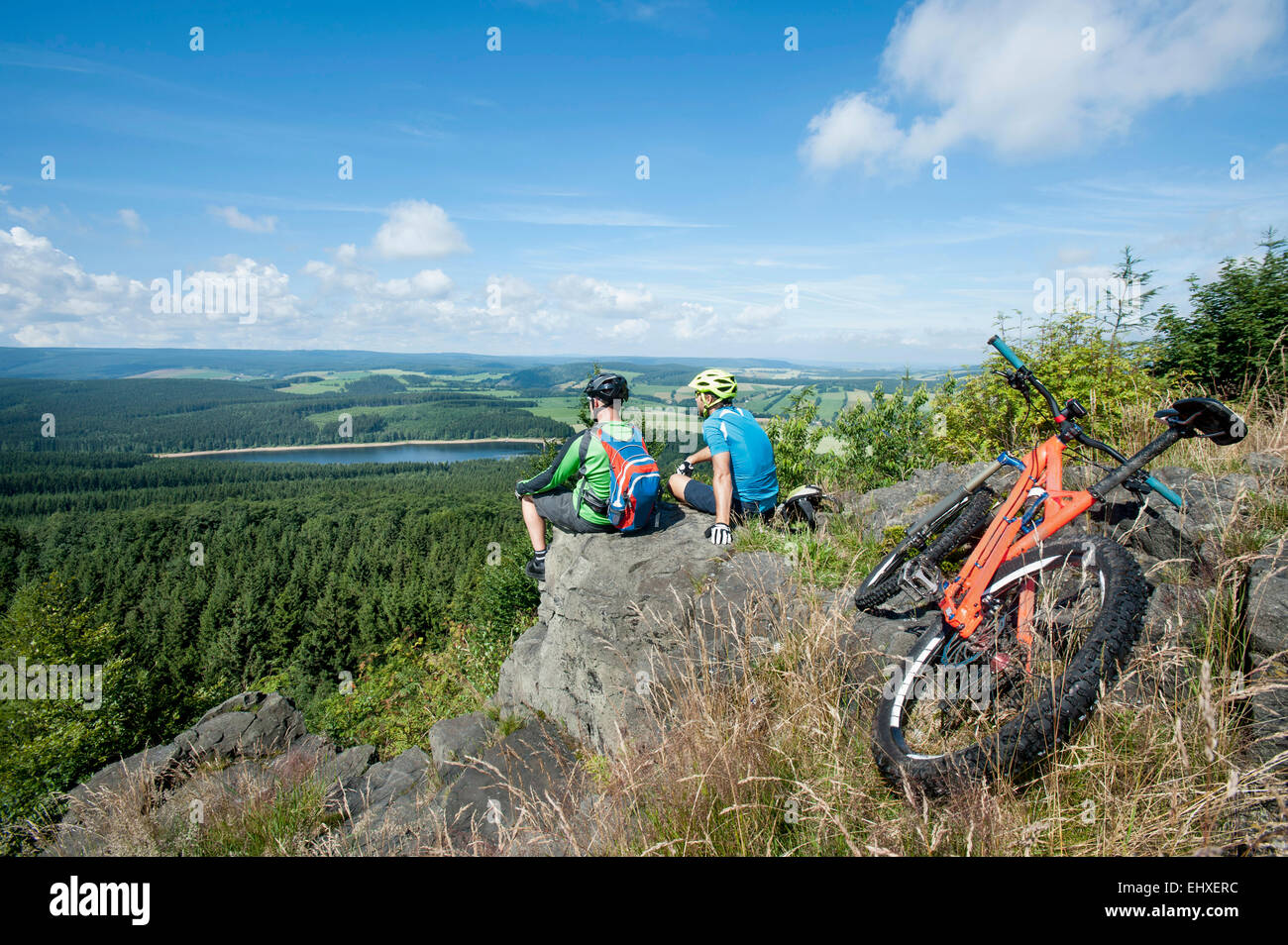 Mountain bikers relaxing on top of mountain, Ore Mountains, Saxony, Germany - Stock Image
