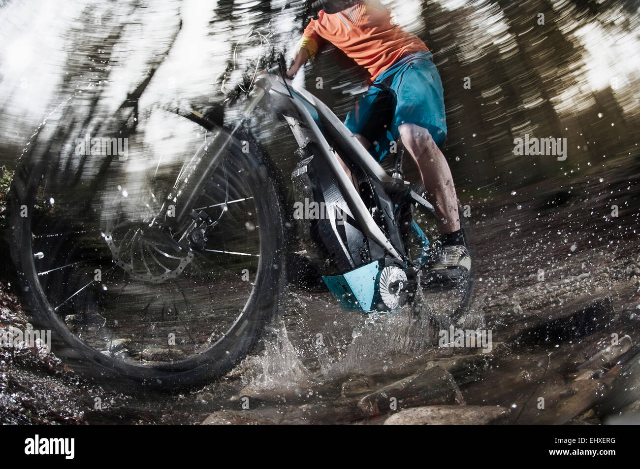 Low section of mountain biker crossing stream in a forest, Bavaria, Germany - Stock Image