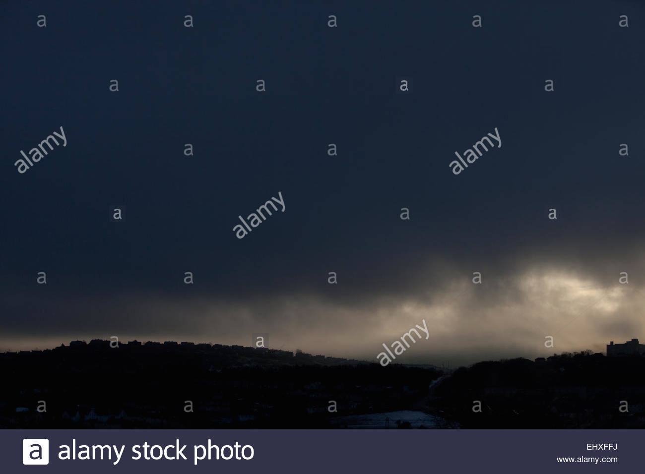 Silhouette row houses dark sky stormy overcast - Stock Image