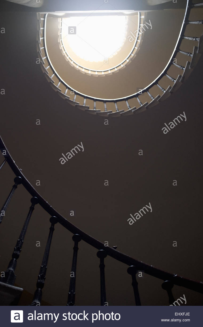Spiral staircase from below light banister - Stock Image