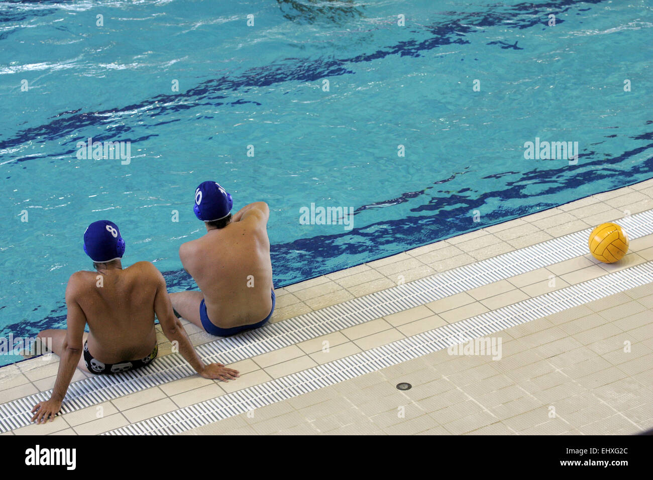 Two Water Polo players sitting poolside - Stock Image