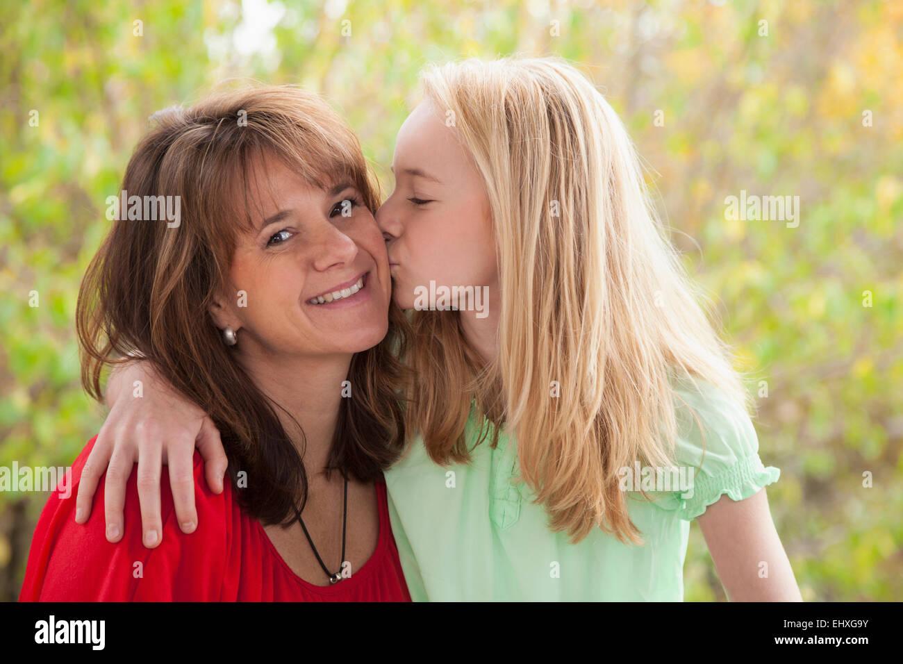 Girl kissing her mother, Bavaria, Germany - Stock Image