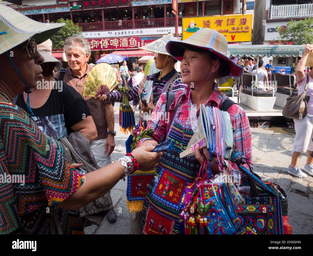 Chinese woman selling hats and other merchandise on the streets of Yangshuo, China Stock Photo