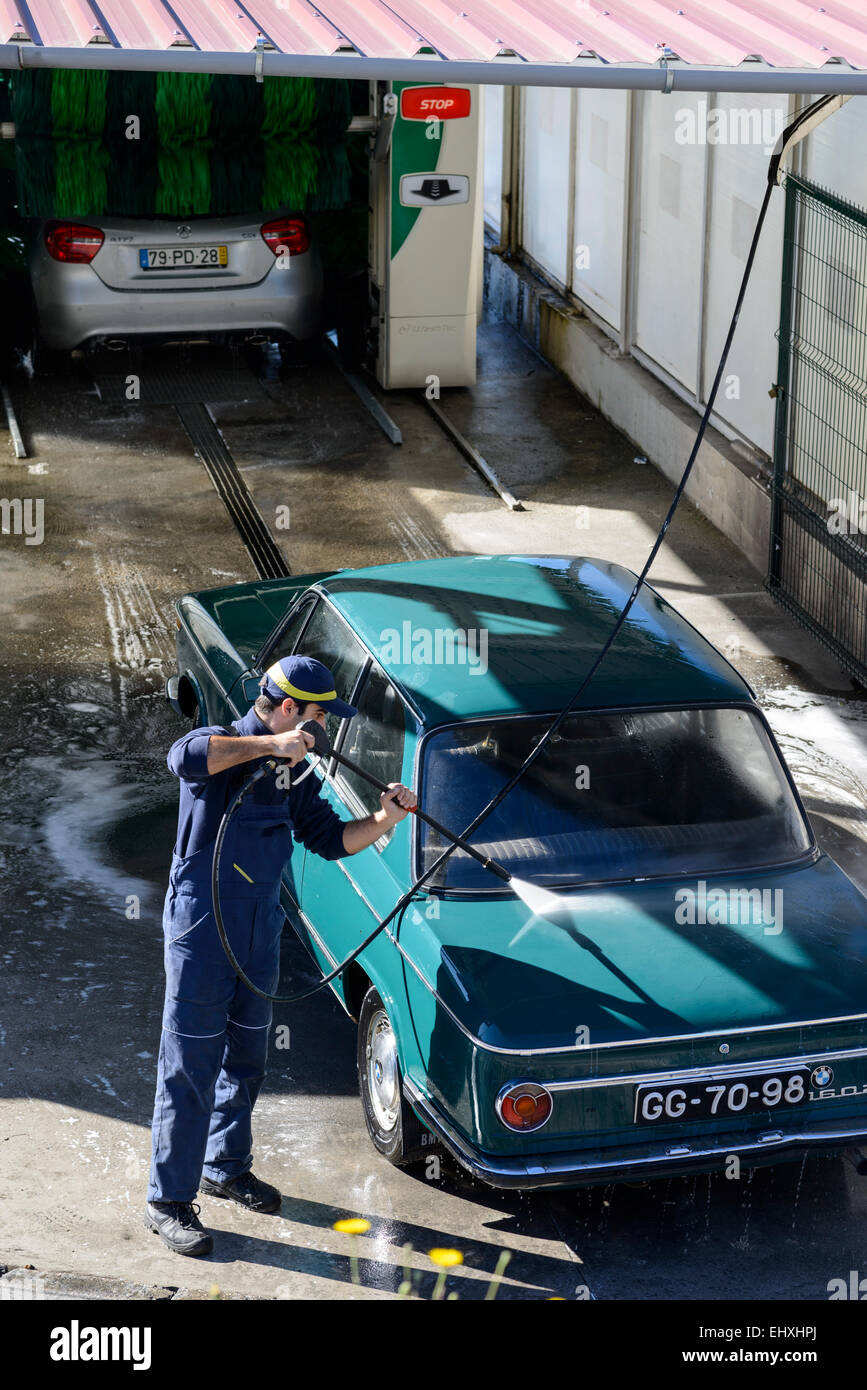 Young Man Washing Car With High Pressure Water Hose At A Professional Car  Wash