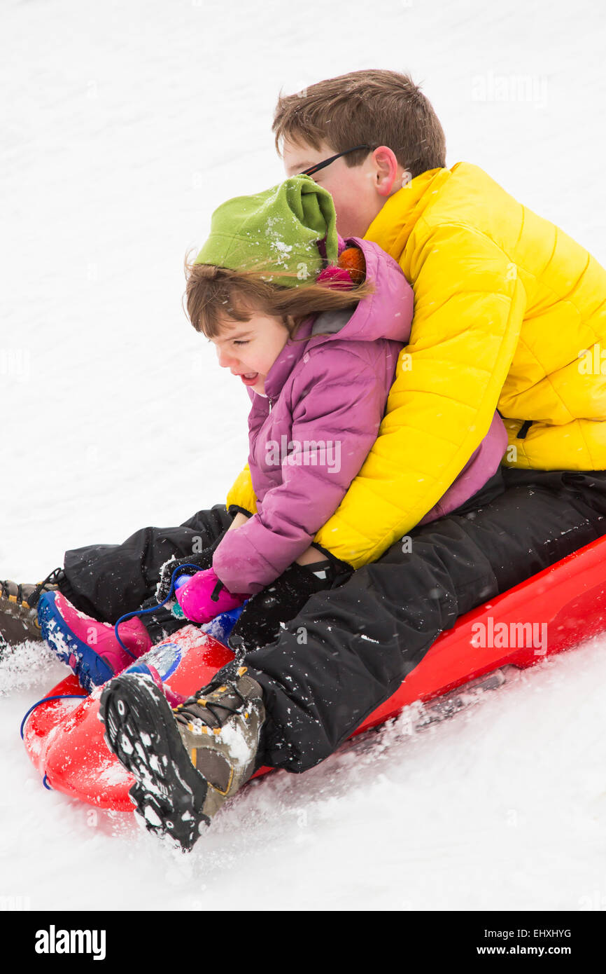 Germany, Swabian mountains, brother and sicster driving downwards on sledge - Stock Image