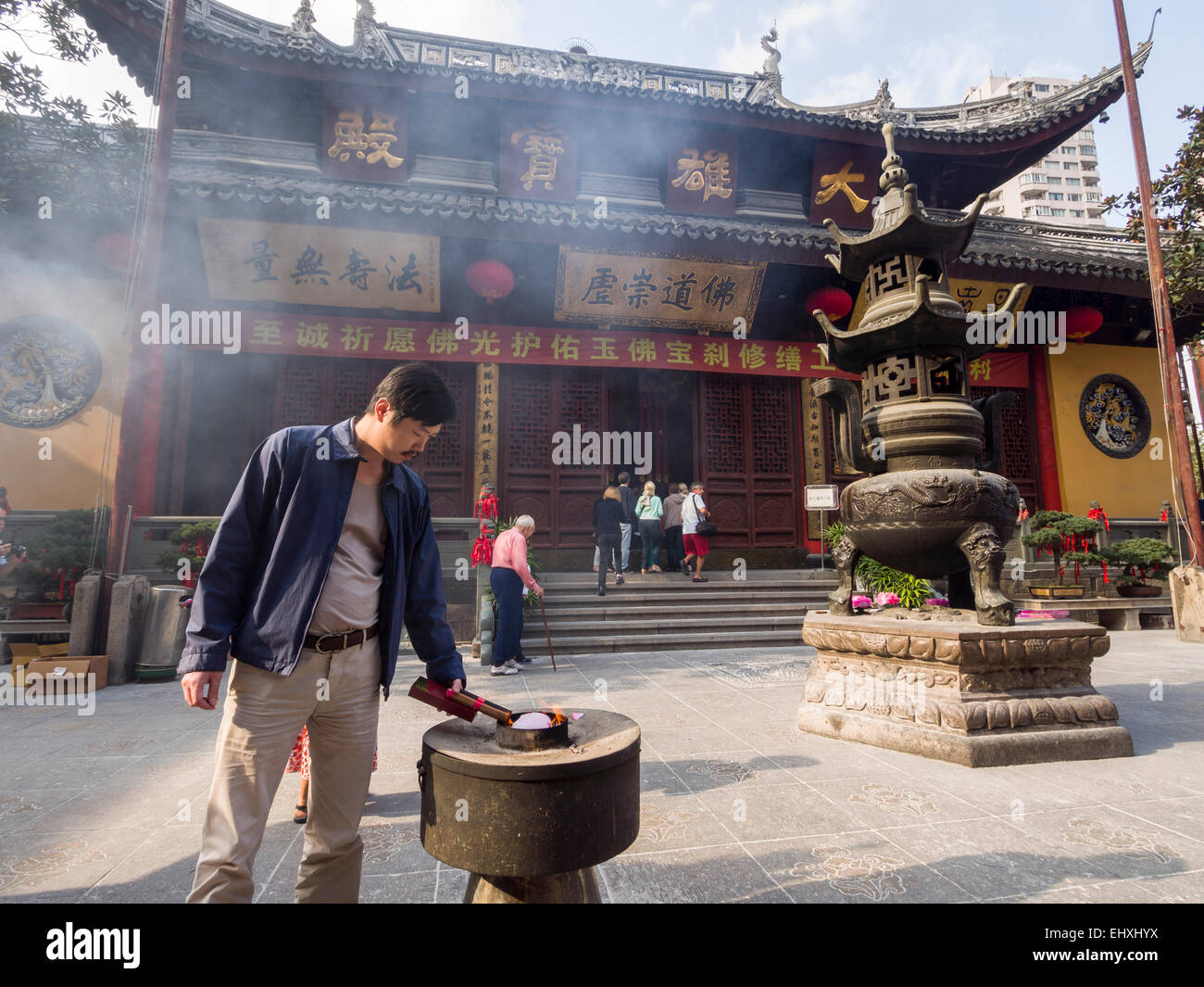 Man lighting joss stick incense at the courtyard of the Jade Buddha temple in Shanghai, China Stock Photo