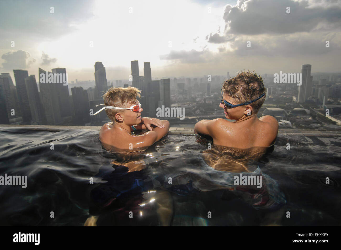 Teenage boys in an infinity pool, Marina Bay Sands, Singapore City, Singapore - Stock Image