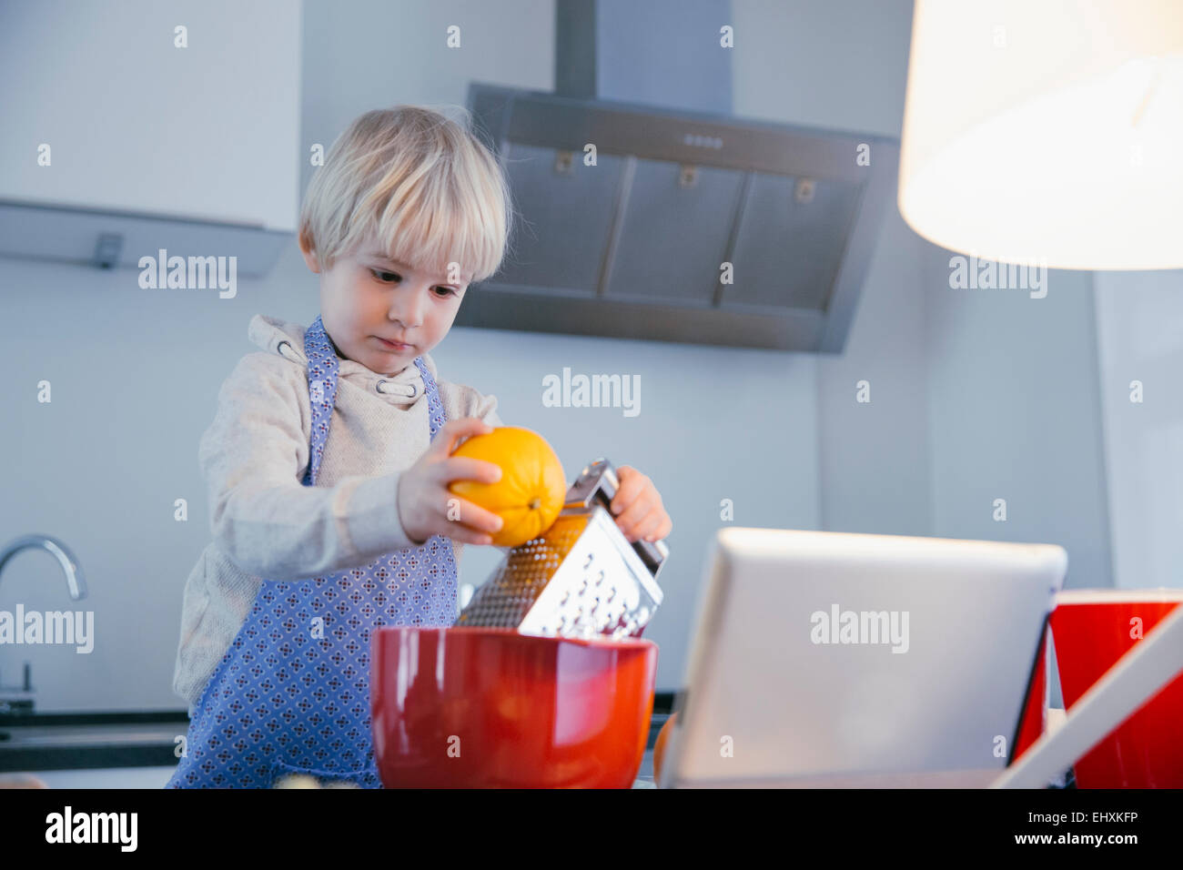 Little boy standing in the kitchen baking with help of digital tablet - Stock Image