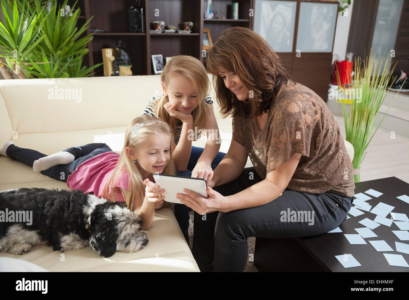 Woman with her two daughters playing games on a digital tablet in a living room, Bavaria, Germany - Stock Image