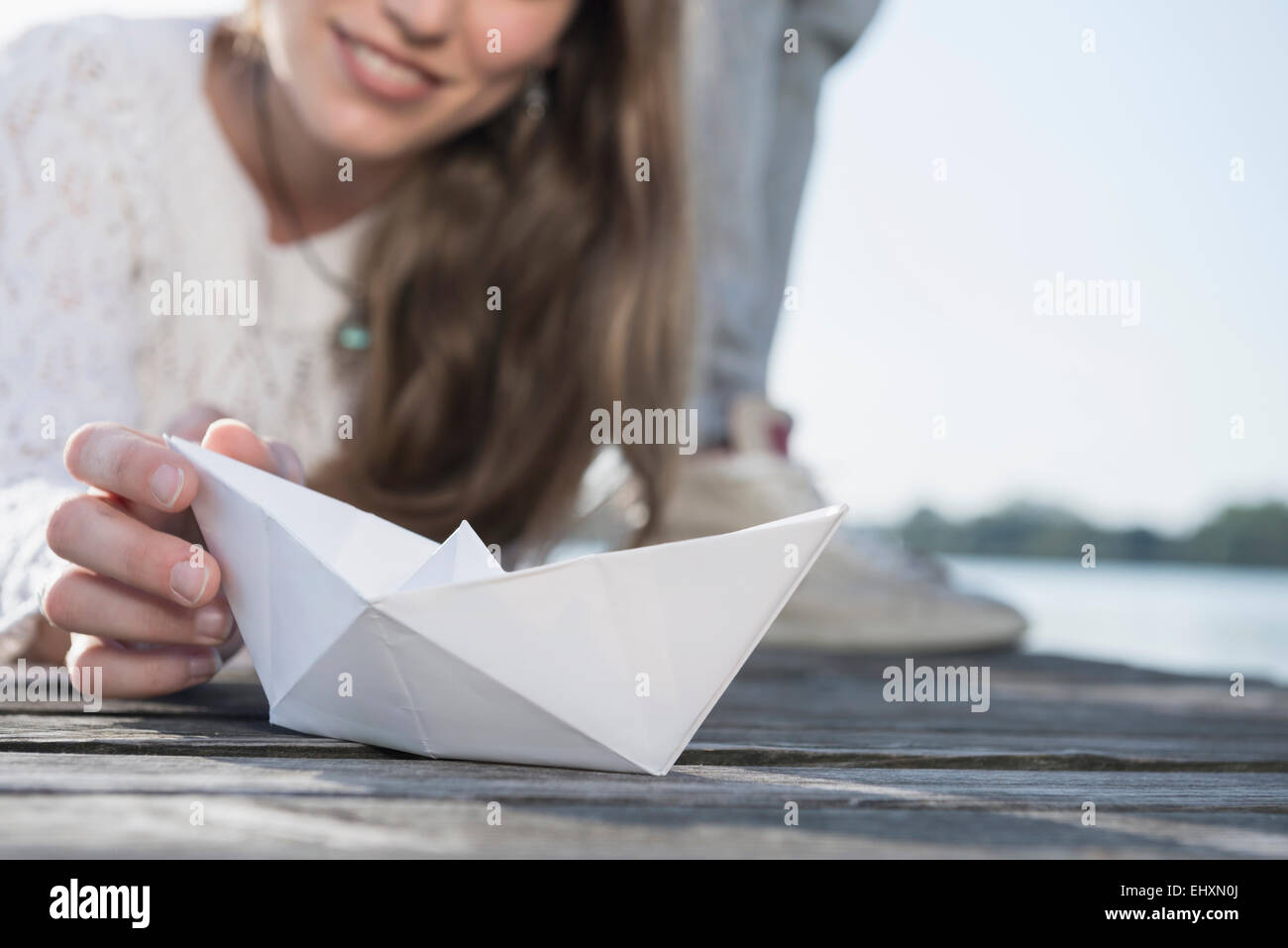 Close up woman holding white paper boat detail - Stock Image