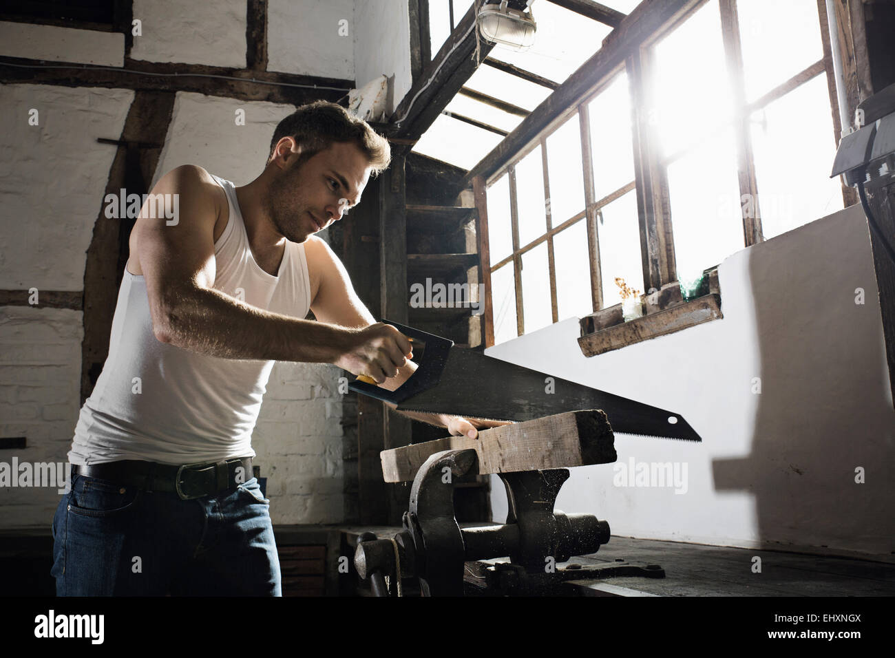 Young man sawing wooden beam in front of his half-timbered house at night - Stock Image
