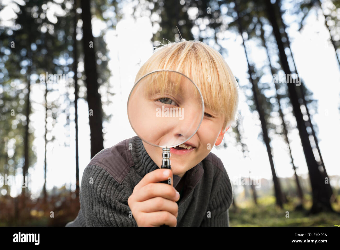 Little boy looking through magnifying glass at viewer - Stock Image