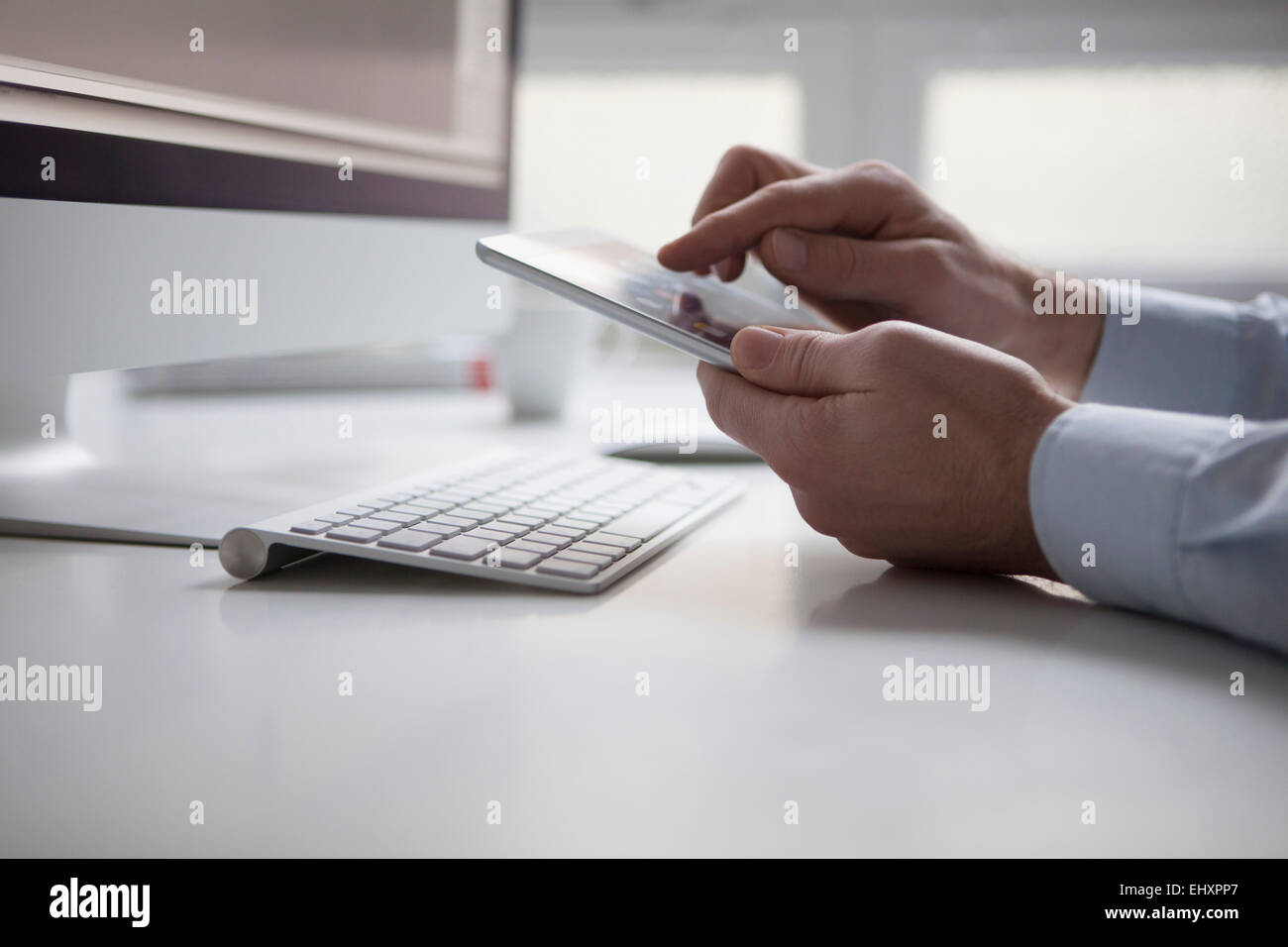 Man's hand typing on touchscreen of digital tablet - Stock Image