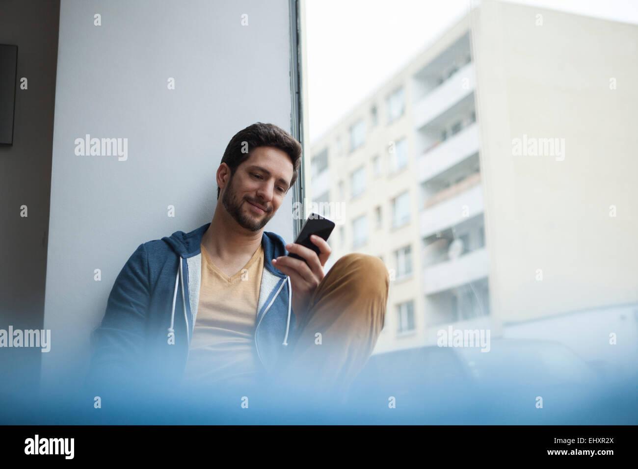 Smiling man reading SMS - Stock Image