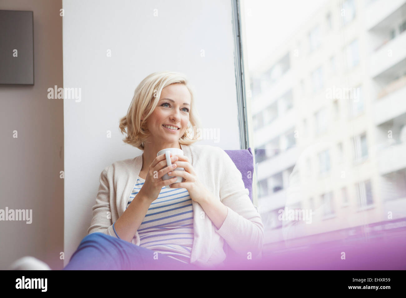 Portrait of smiling woman looking through window - Stock Image