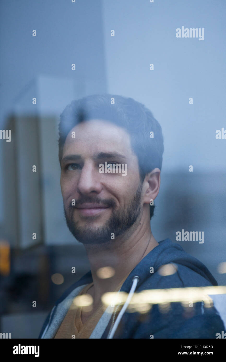 Portrait of smiling man with beard looking through window - Stock Image
