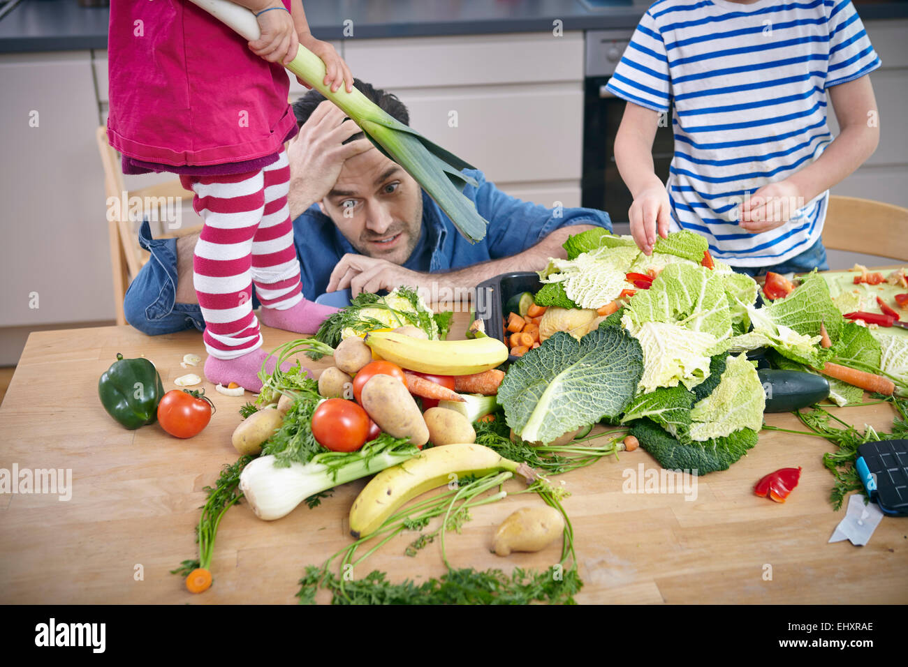 Desperate father trying to preparie food in chaos - Stock Image