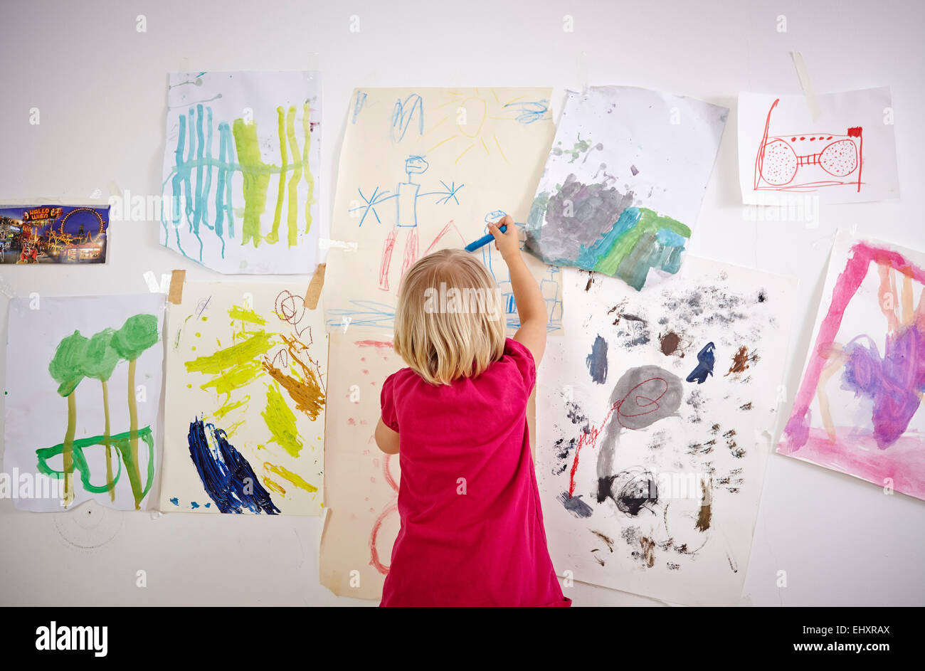 Little girl painting on wall of children's room, rear view - Stock Image