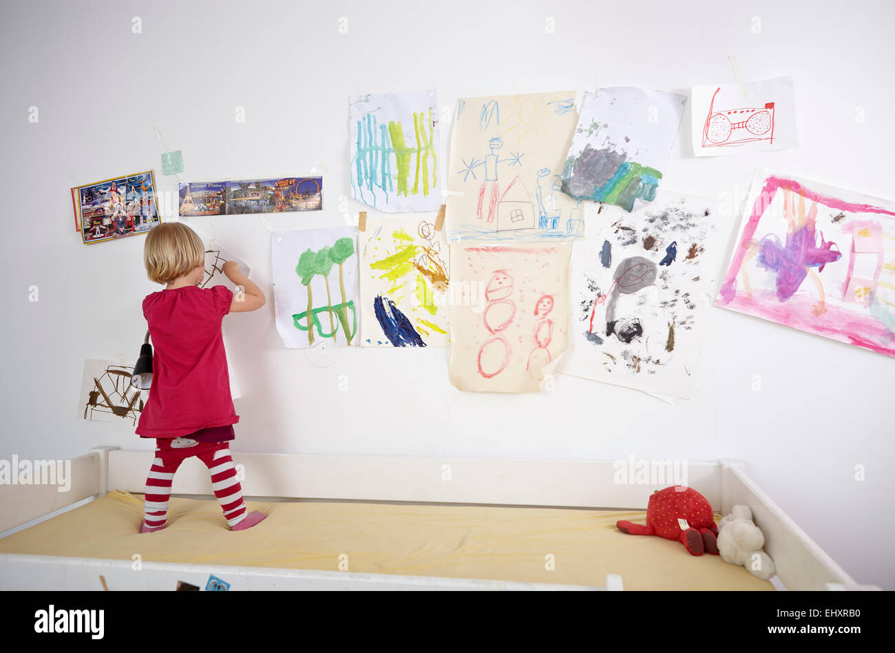 Little Girl Painting On Wall Of Children S Room Rear View Stock