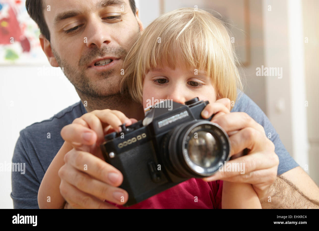 Father explaining analogue camera to daughter - Stock Image