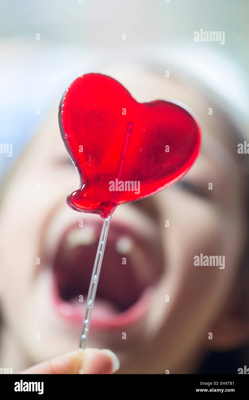Girl's open mouth and heart-shaped lollipop - Stock Image