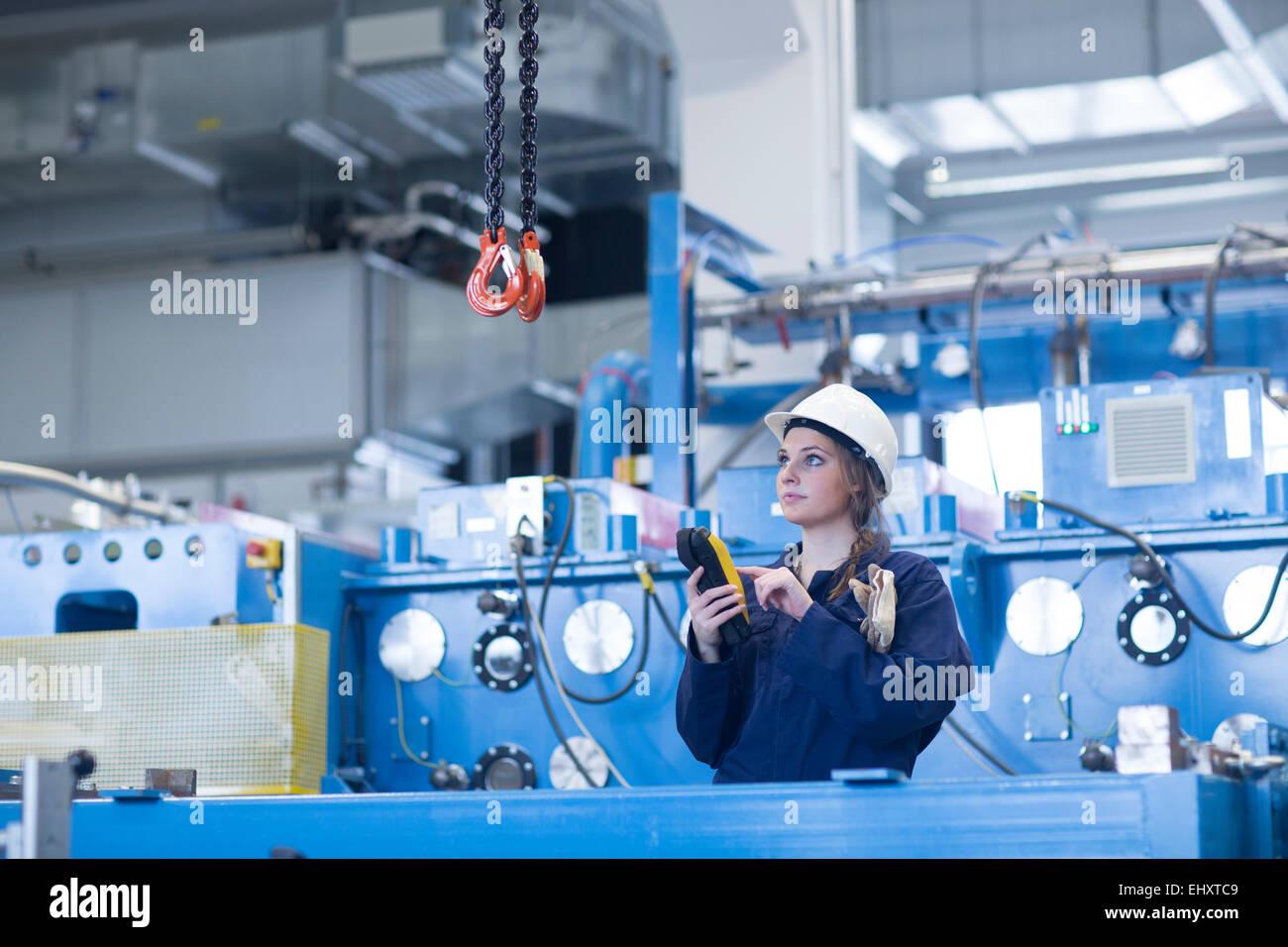 Technician in factory hall using regulator for hook - Stock Image