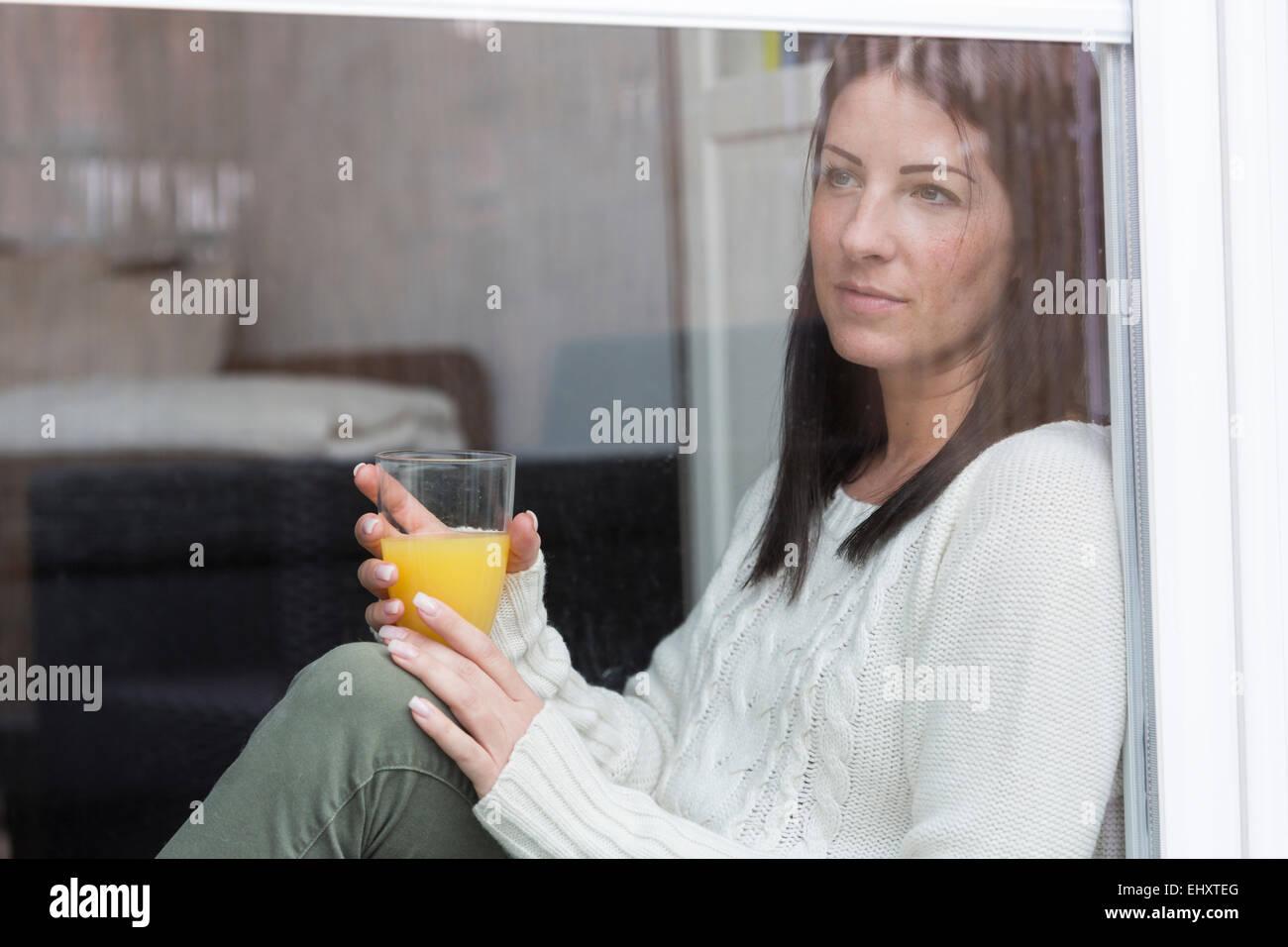 Woman with glass of orange juice looking through window - Stock Image