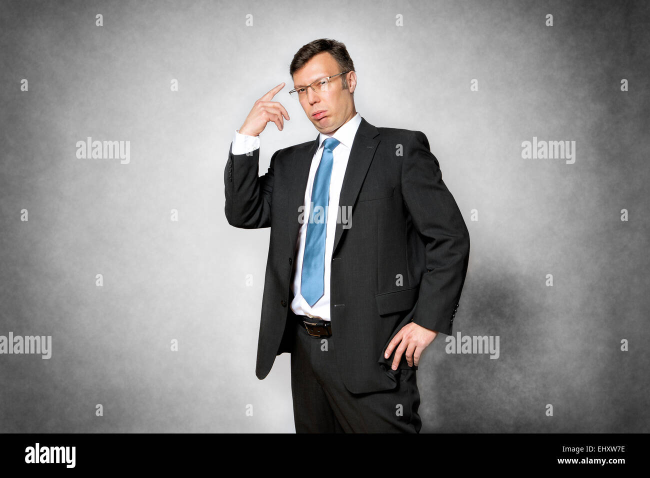 Image of conceited business man in dark suit pointing his finger to his head - Stock Image