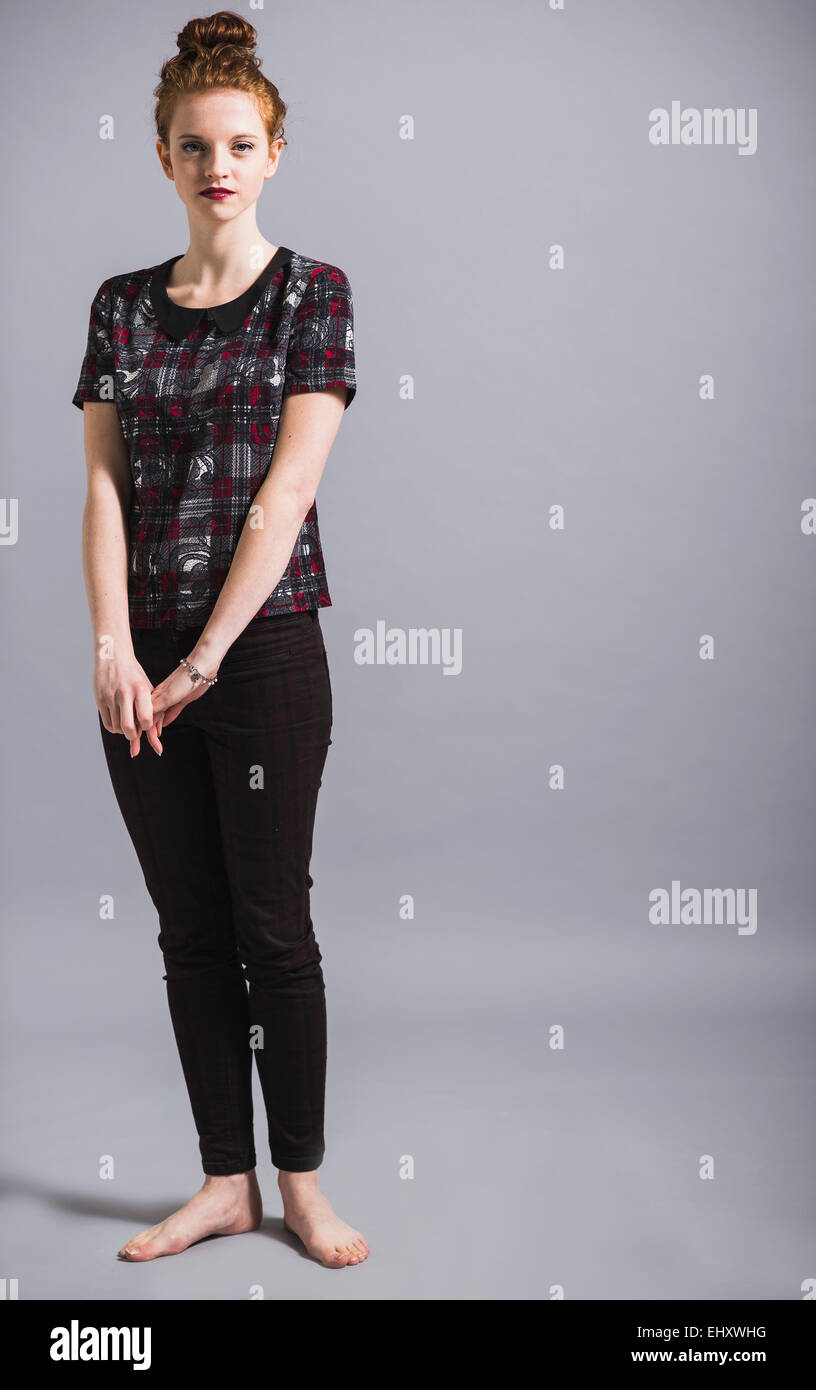 Portrait of barefooted young woman wearing pants and top - Stock Image
