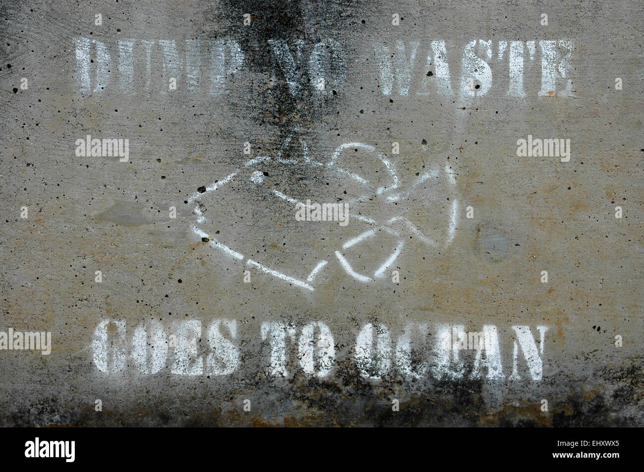 Weathered 'dump no waste goes to ocean' warning sign on concrete - Stock Image