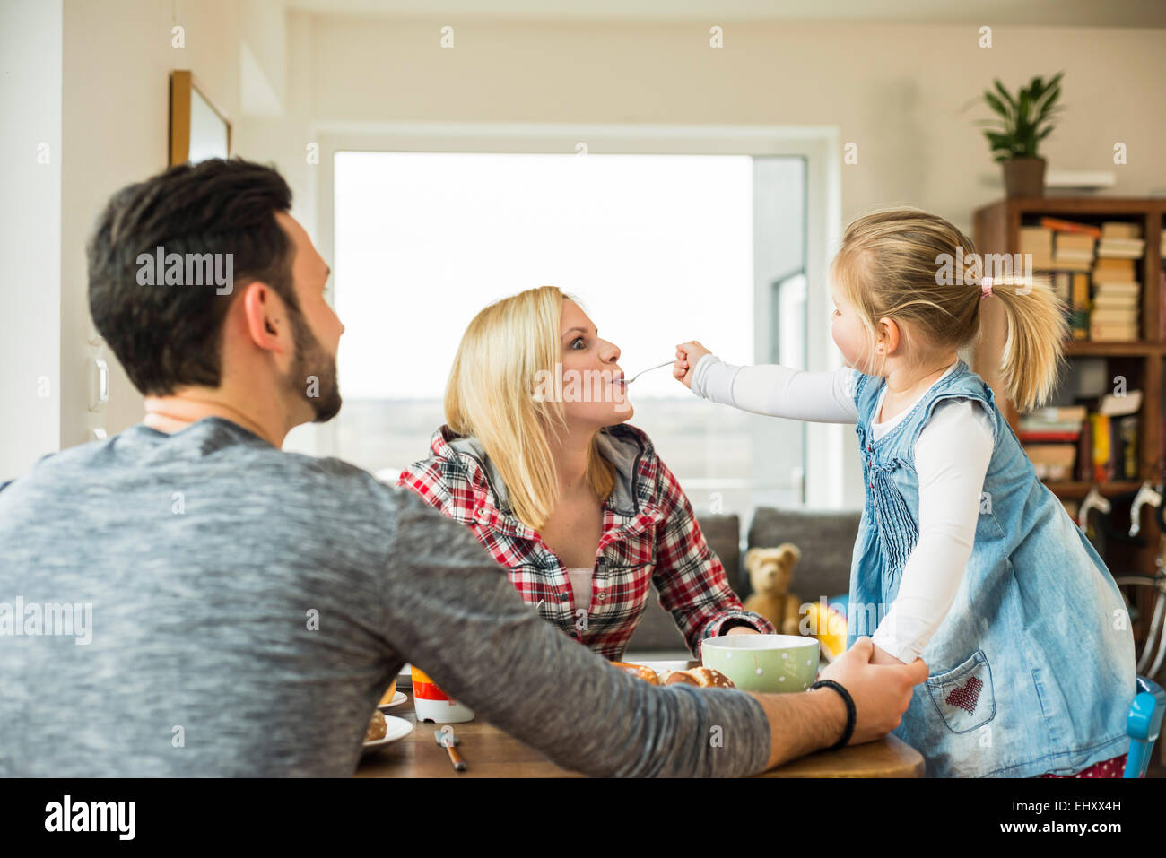 Daughter feeding mother at dining table - Stock Image