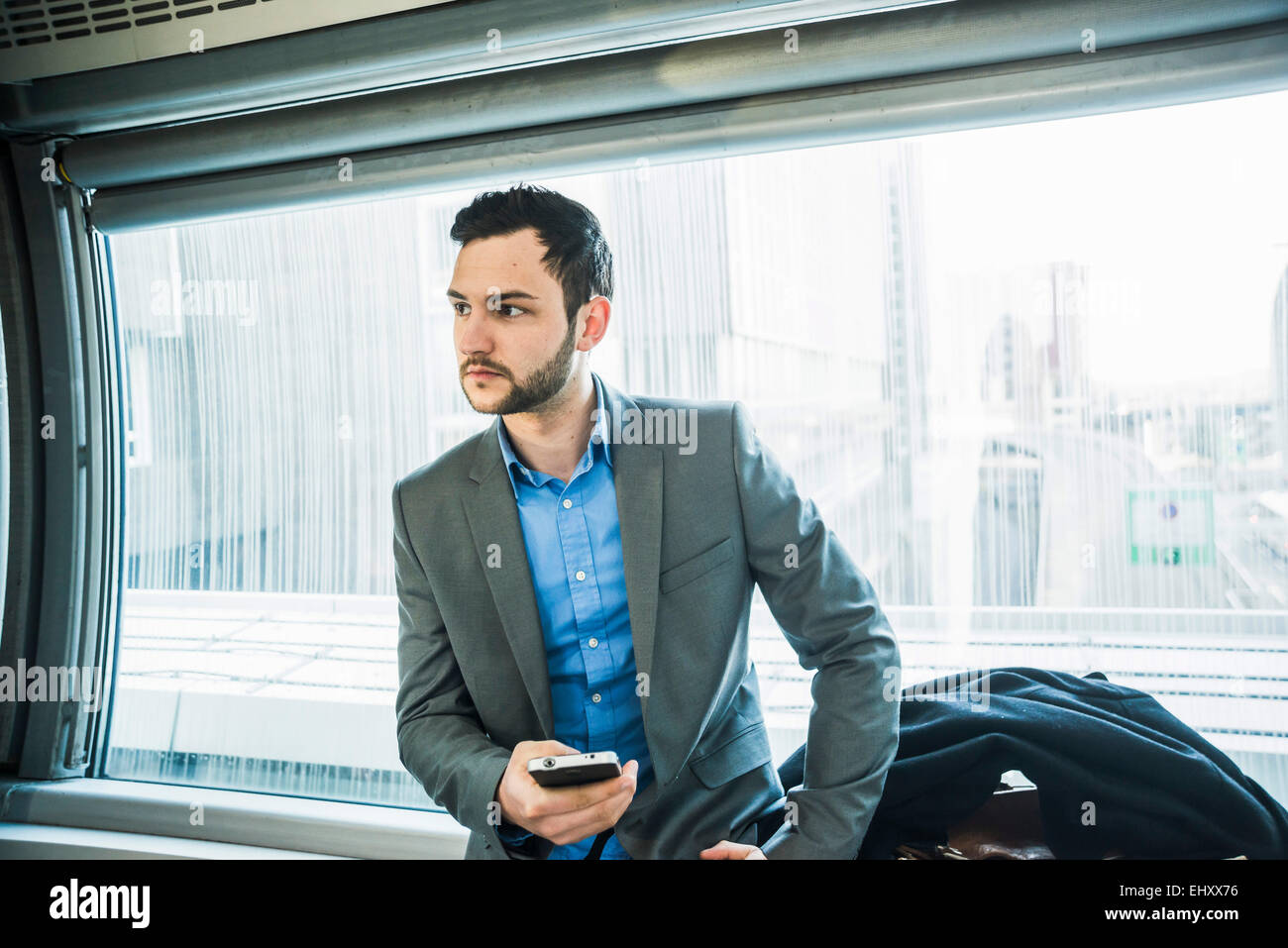 Young businessman with cell phone in underground train - Stock Image
