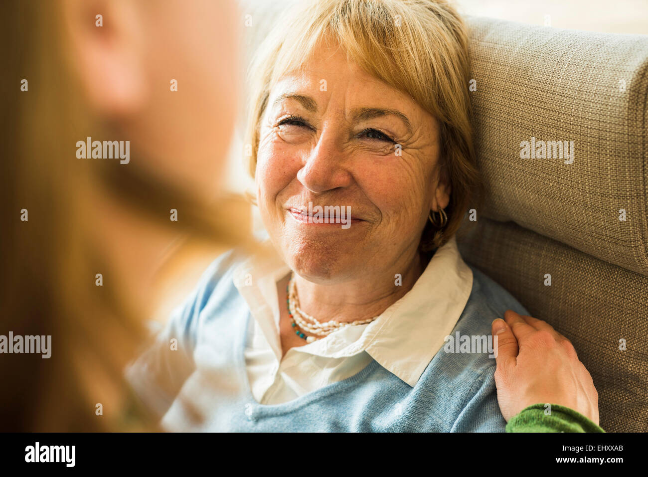 Smiling grandmother looking at adult granddaughter - Stock Image
