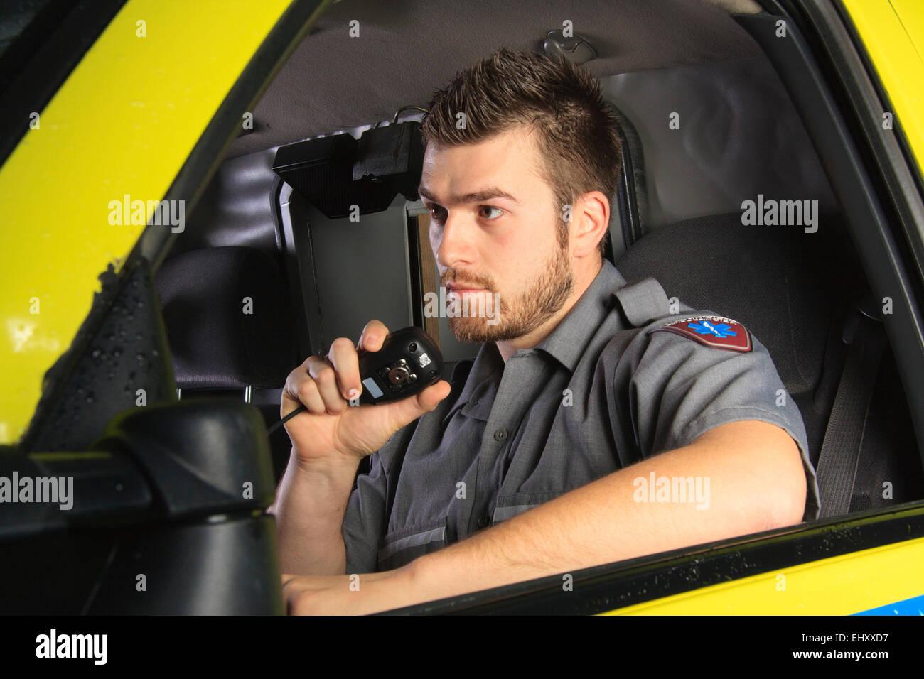A paramedic at the wheel of his ambulance - Stock Image