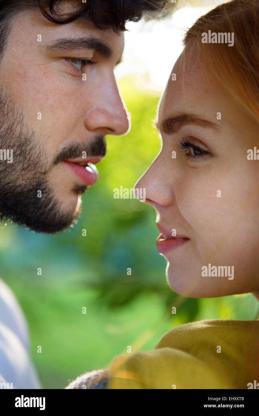 Young couple sharing an intimate moment outdoors - Stock Image