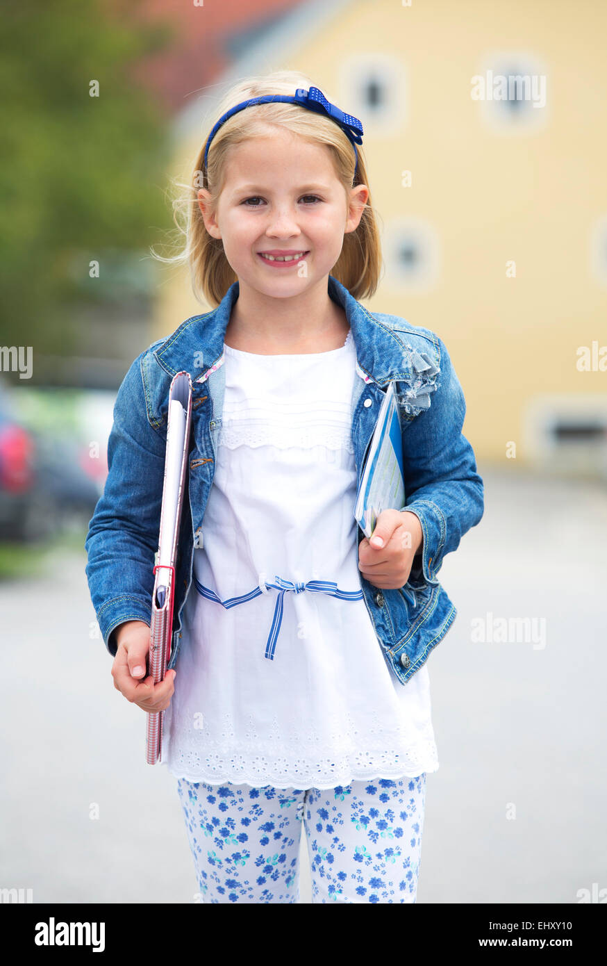 Portrait of smiling little girl with file and exercise book - Stock Image