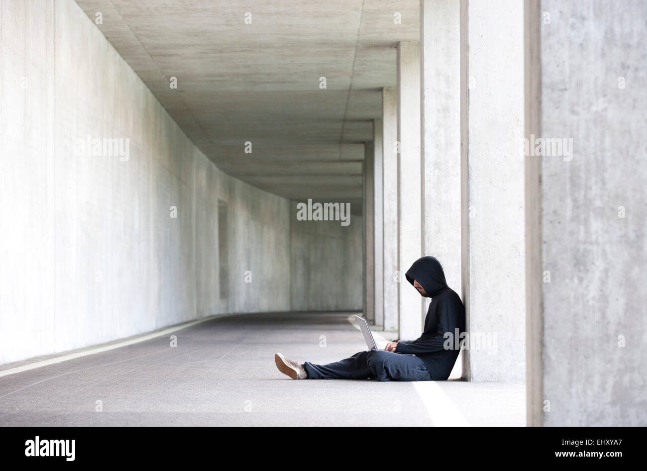 Hacker with laptop sitting in an underground car park - Stock Image