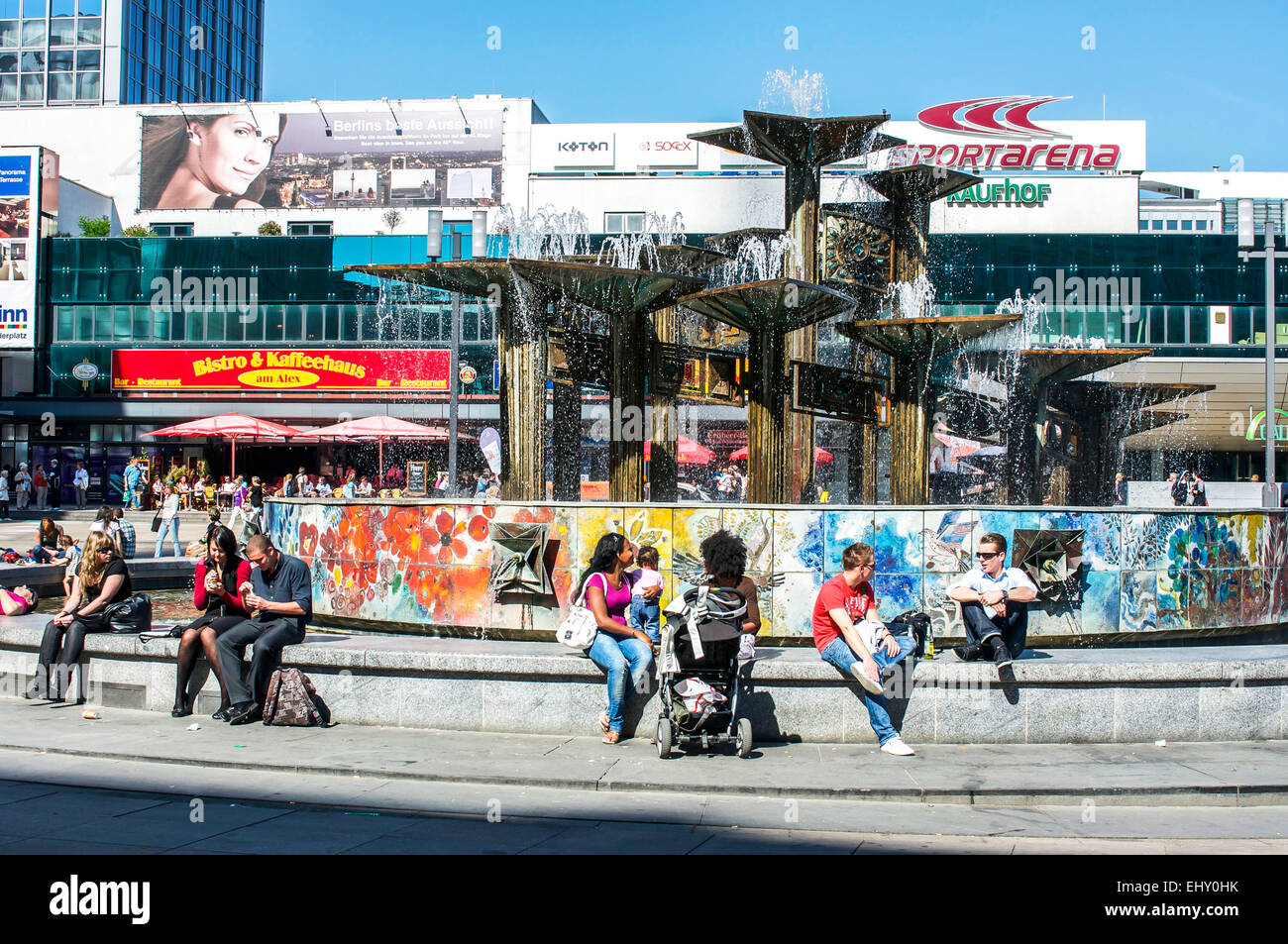 People cooling off around a fountain at Alexanderplatz in Berlin, Germany on a hot day. - Stock Image
