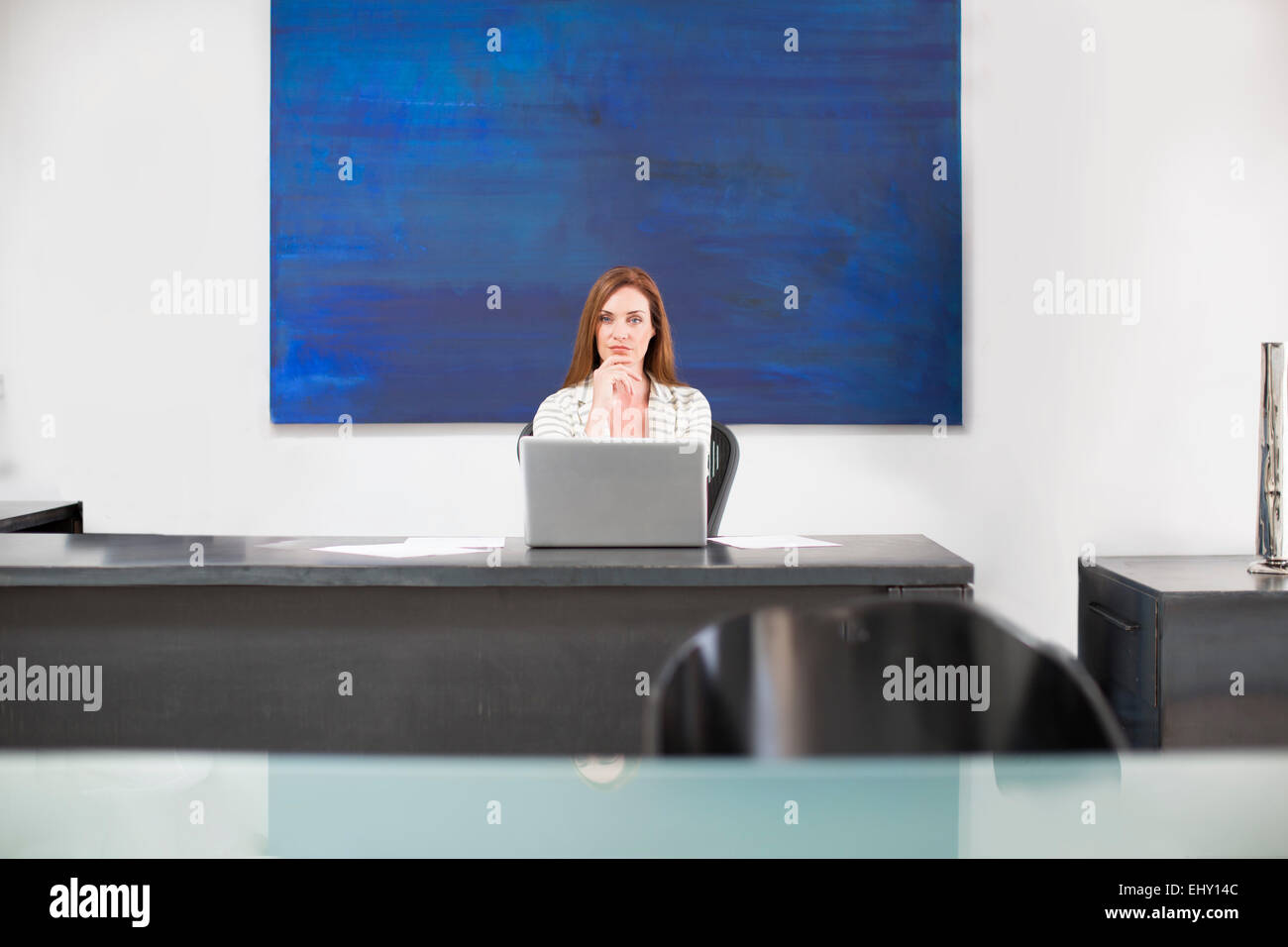 Confident businesswoman in modern office - Stock Image
